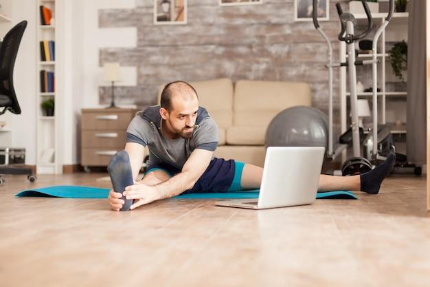 Мужчина учится растягивать свое тело, глядя на онлайн-курс на ноутбуке во время изоляции от коронавируса.