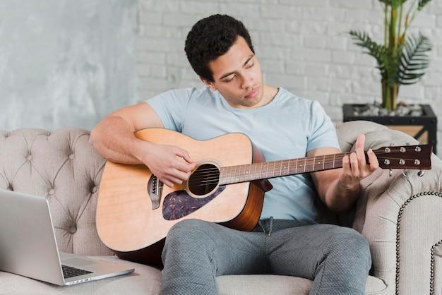オンラインでギターの弾き方を学ぶ男
