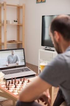 Человек учится играть в шахматы по видеозвонку во время карантина.