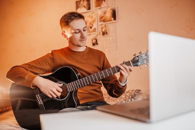 Человек учится играть на гитаре с помощью онлайн-обучения дома