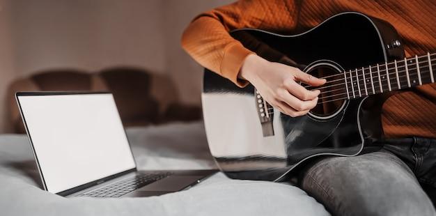 Человек учится играть на гитаре с помощью онлайн-обучения дома.