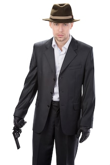 Man in leather gloves and suit and gun.