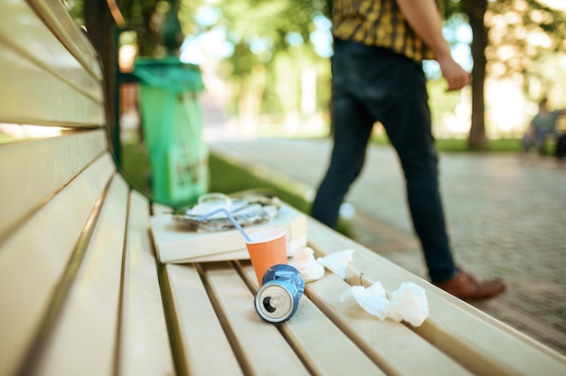 Man left trash on bench near a bin in park, volunteering motivator. ecological restoration, eco lifestyle, ecology care, environment cleaning concept