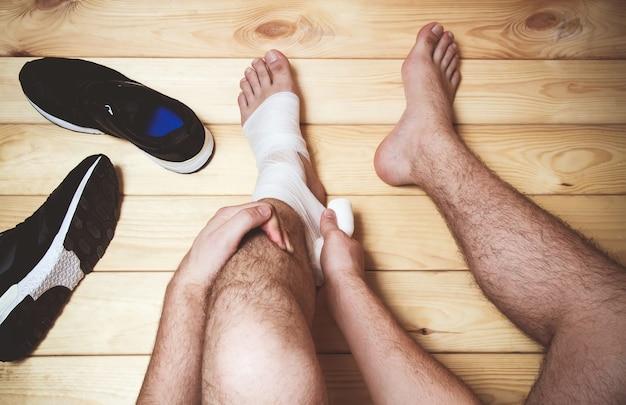 Повязка на ногу человека, сидящего на деревянном полу