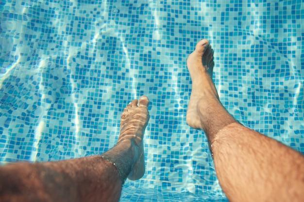 수영장에서 발을 가진 남자 다리.