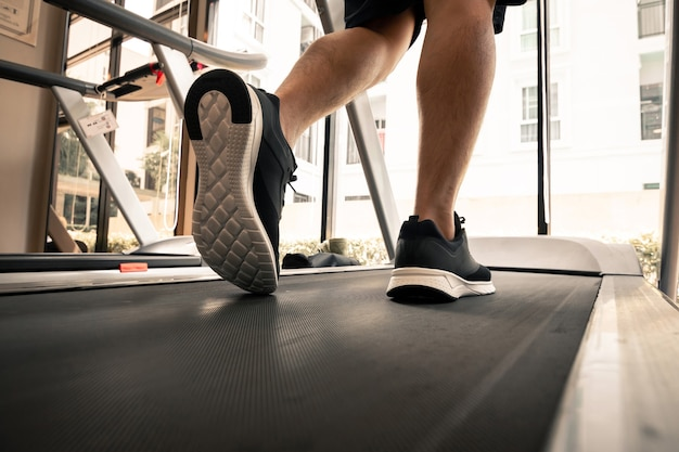 Man legs with sport shoes running on treadmill in fitness gym.