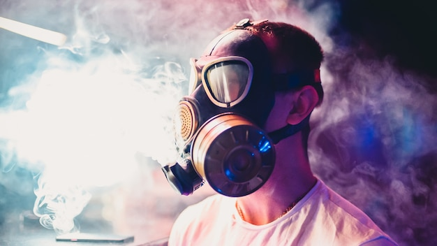 Man lets clouds of hookah smoke in a gas mask