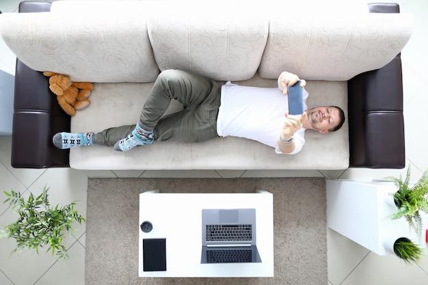 남자는 소파에 누워 현대 스마트 폰을 손에 잡으십시오. 셀카 사진을 만듭니다. 모바일 애플리케이션 개념을 사용합니다. 소셜 미디어 중독자