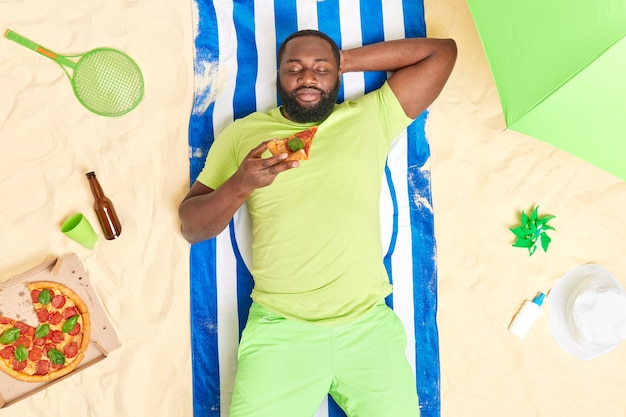Man lies at beach eats pizza has good rest during summer holidays dressed in green t shirt and shorts poses at towel on sand with various items around