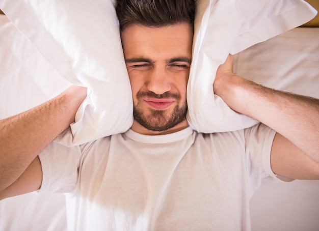 A man lies in bed and holds his ears with a pillow.