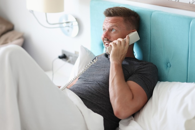 Man lies in bed in hotel room and talk on phone.