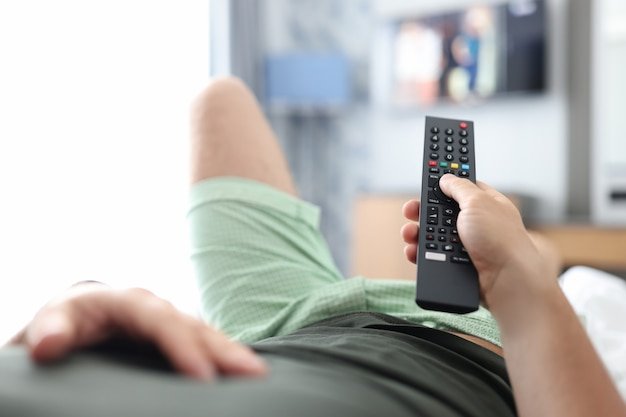 Man lies on bed and switches buttons on tv remote control remote admission concept