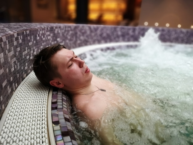 A man lies in a bubbling jacuzzi bath in a spa hotel, relaxing in the pool.
