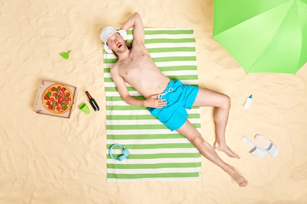Man lies on green striped towel at sandy beach eats delicious pizza drinks beer enjoys lazy day sunny weather wears panama and blue shorts