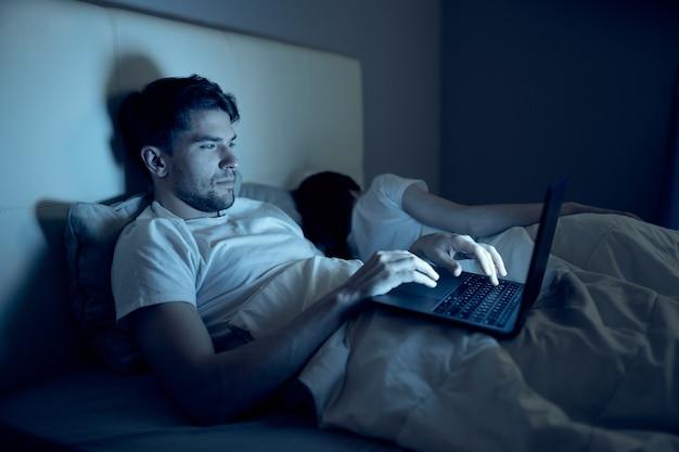 Человек лежит в постели ночью перед отдыхом для ноутбука