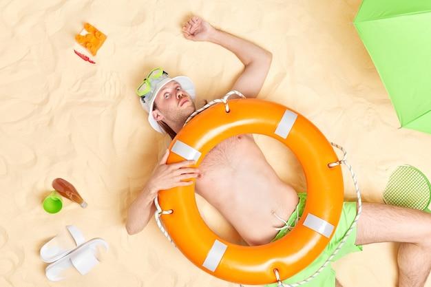 男は救命浮輪が高温でショックを受けた日よけ帽シュノーケリングマスクを身に着けている砂の上に横たわっています。俯瞰図