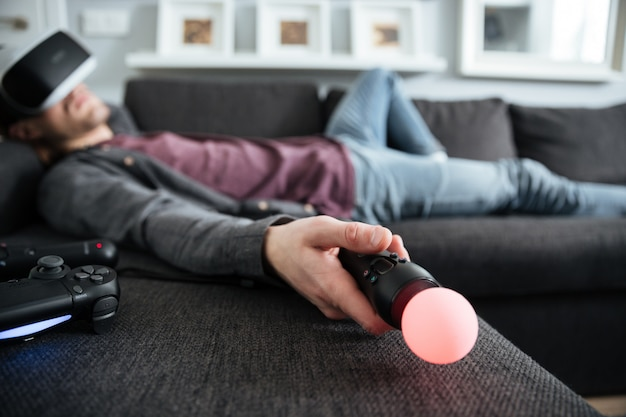 Человек лежит на диване в очках виртуальной реальности, держа джойстик.