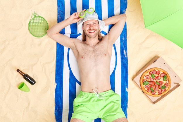 Man lies on striped towel enjoys lazy summer day at beach wears sun hat snorkeling mask eats appetizing pizza has relax looks happily at camera sunbathes rests on tropical resort