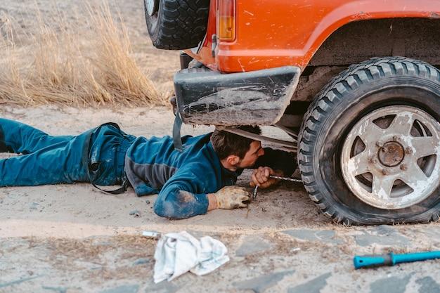 男は未舗装の道路で4 x 4車の下にあります。