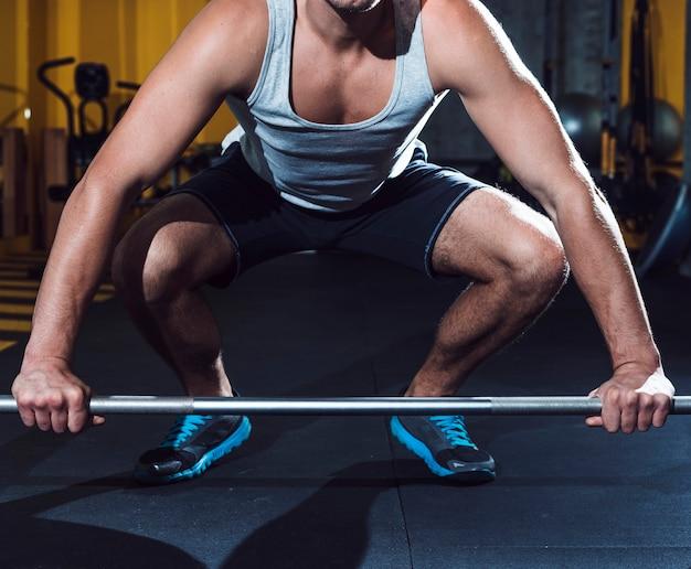 Мужчина поднимает штангу в фитнес-клубе