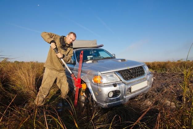 하이 잭에 의해 깊은 진흙에 갇힌 차를 들어 올리는 남자