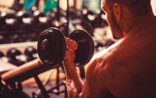 Человек, снимающий гантели в тренажерном зале, делая упражнения для мышц. бодибилдер работает с гантелями в тренажерном зале. культурист человек делает упражнения с гантелями. человек фитнеса поднимаясь гантели.