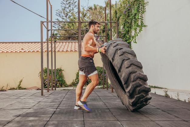 Man lifting tractor wheel