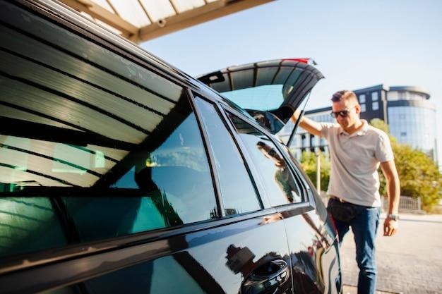 Мужчина поднимает дверь багажника черного автомобиля