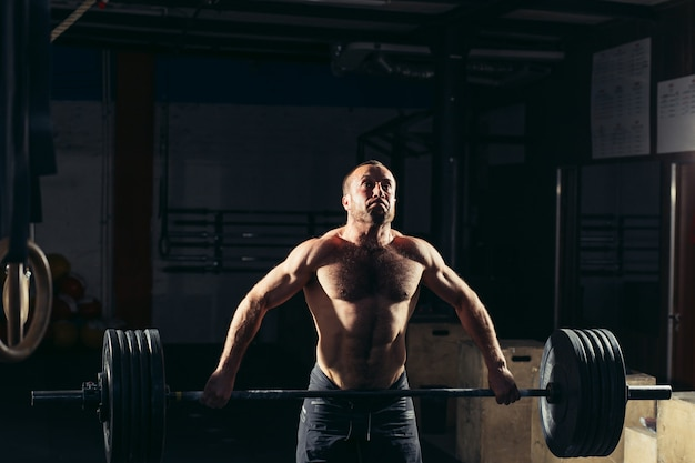 Man lifting weights. muscular man workout in gym doing exercises with barbell