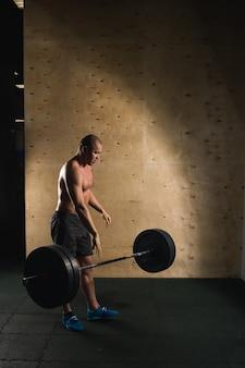 Человек, поднятие тяжестей. мускулистый мужчина тренировки в тренажерном зале, делая упражнения со штангой