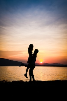 A man lifting a woman background is lake mountain and sunset