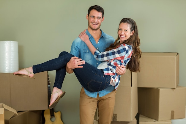 Man lifting woman in his arms in their new house
