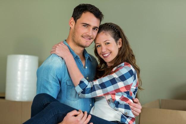 Мужчина поднимает женщину на руках в своем новом доме