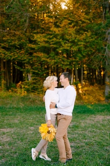 Man in light clothes smiling hugs woman with a bouquet of yellow leaves in the autumn forest