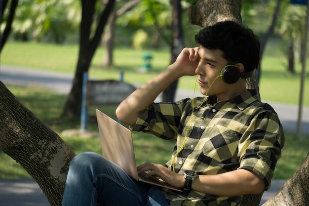 Человек слушает музыку в наушниках в парке