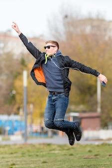 Man listening to music on earphones while jumping outside