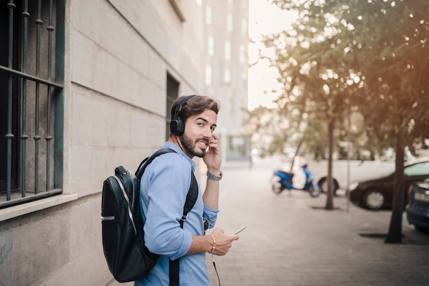 Man listening to music on headphone looking at camera