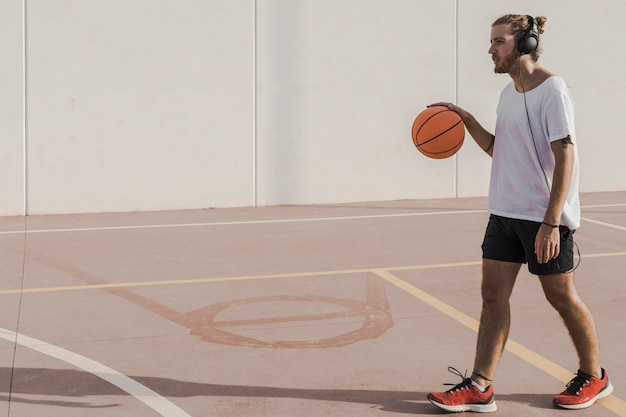 Man listening to music on headphone walking with basketball in court