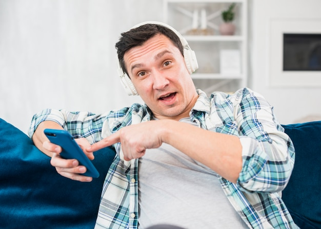 Man listening music in headphones and pointing at smartphone on sofa