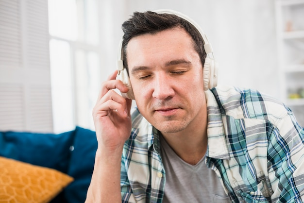Man listening music in headphones on sofa