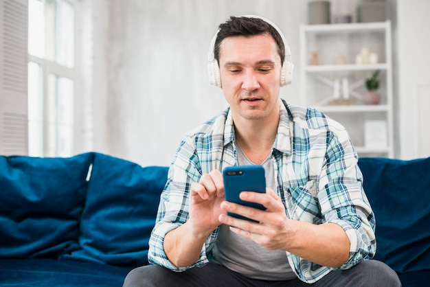 Man listening music in headphones and using smartphone on sofa