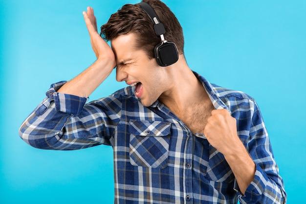 Uomo che ascolta musica su cuffie wireless divertendosi in stile moderno felice umore emotivo isolato su blue