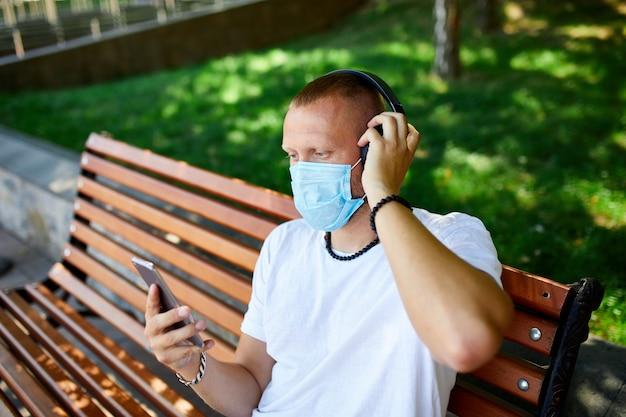 Человек слушает музыку в наушниках, используя смартфон в защитной маске на открытом воздухе в парке, новый нормальный образ жизни, карантин, коронавирус