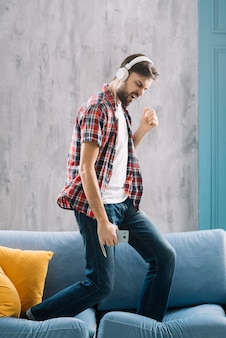Man listening to music and dancing on sofa