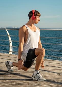 エクササイズ中にヘッドフォンでビーチで音楽を聴いている男