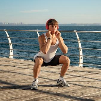 運動しながらビーチで音楽を聴いている男