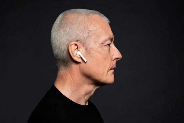 イヤホンから音楽を聴いている男