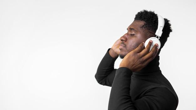 ヘッドフォンのコピースペースで音楽を聴いている男