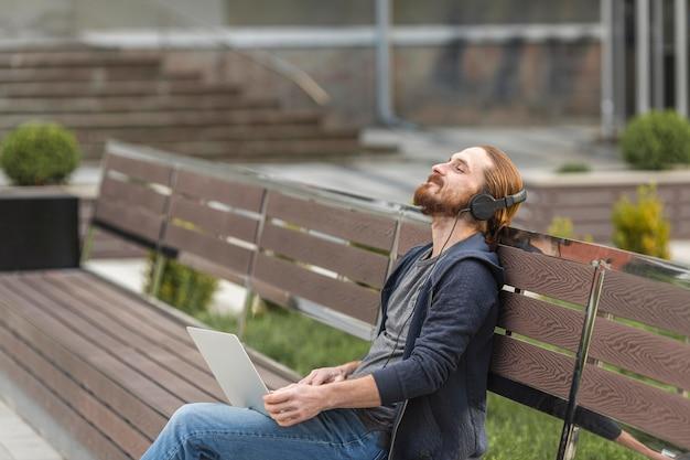 市内の屋外のヘッドフォンで音楽を聞いている男性