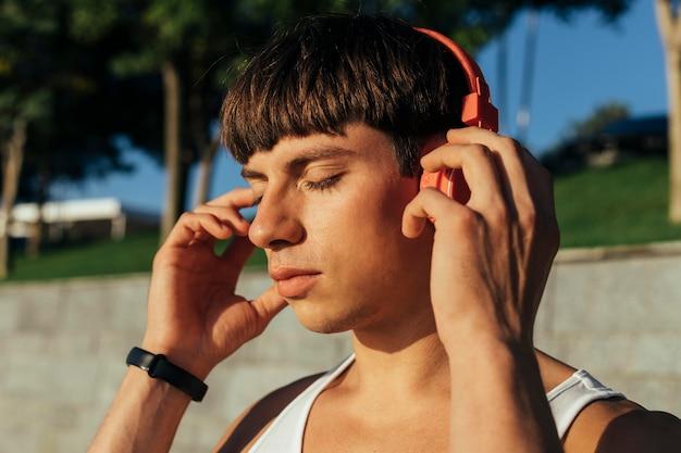 屋外でヘッドフォンで音楽を聴いている男性